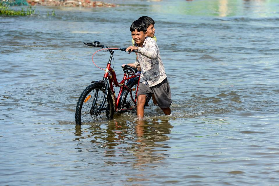 Children push a bicycle on a flooded street following heavy rains in Hyderabad on October 16, 2020. (Photo by NOAH SEELAM / AFP) (Photo by NOAH SEELAM/AFP via Getty Images)