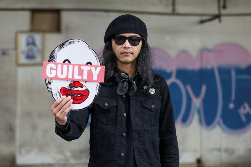 Malaysian artist and activist Fahmi Reza poses for a picture holding his artwork bearing an image of former Prime Minister Najib Razak, during an interview with Reuters, in Kuala Lumpur