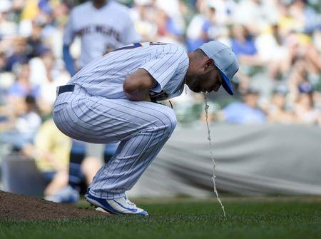 Jun 17, 2018; Milwaukee, WI, USA; Milwaukee Brewers pitcher Adrian Houser (37) falls ill during the game against the Philadelphia Phillies in the eighth inning at Miller Park. Mandatory Credit: Benny Sieu-USA TODAY Sports