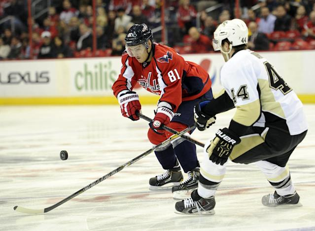Washington Capitals defenseman Dmitry Orlov (81) goes for the puck against Pittsburgh Penguins defenseman Brooks Orpik (44) during the first period of an NHL hockey game, Monday, March 10, 2014, in Washington. (AP Photo/Nick Wass)