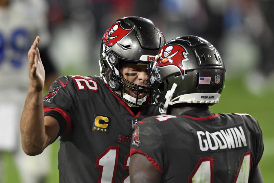Tampa Bay Buccaneers quarterback Tom Brady (12) celebrates with wide receiver Chris Godwin (14) after Godwin caught a touchdown pass during the second half of an NFL football game against the Los Angeles Rams Monday, Nov. 23, 2020, in Tampa, Fla. (AP Photo/Jason Behnken)