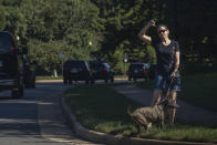 A resident walking her dog gestures as the motorcade of President Donald Trump drives by towards the Trump National Golf Club in Sterling, Va., Sunday, Aug. 30, 2020. (AP Photo/Manuel Balce Ceneta)