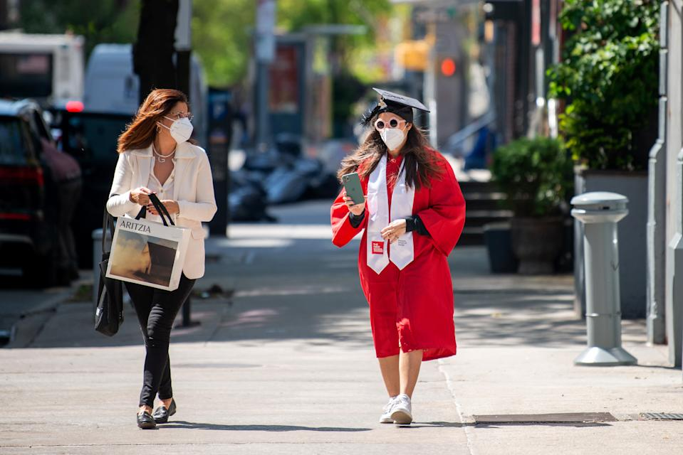 A mother wearing a mask walks with her daughter wearing a mask, cap and gown amid the coronavirus pandemic on May 14, 2020 in New York City. (Photo by Alexi Rosenfeld/Getty Images)