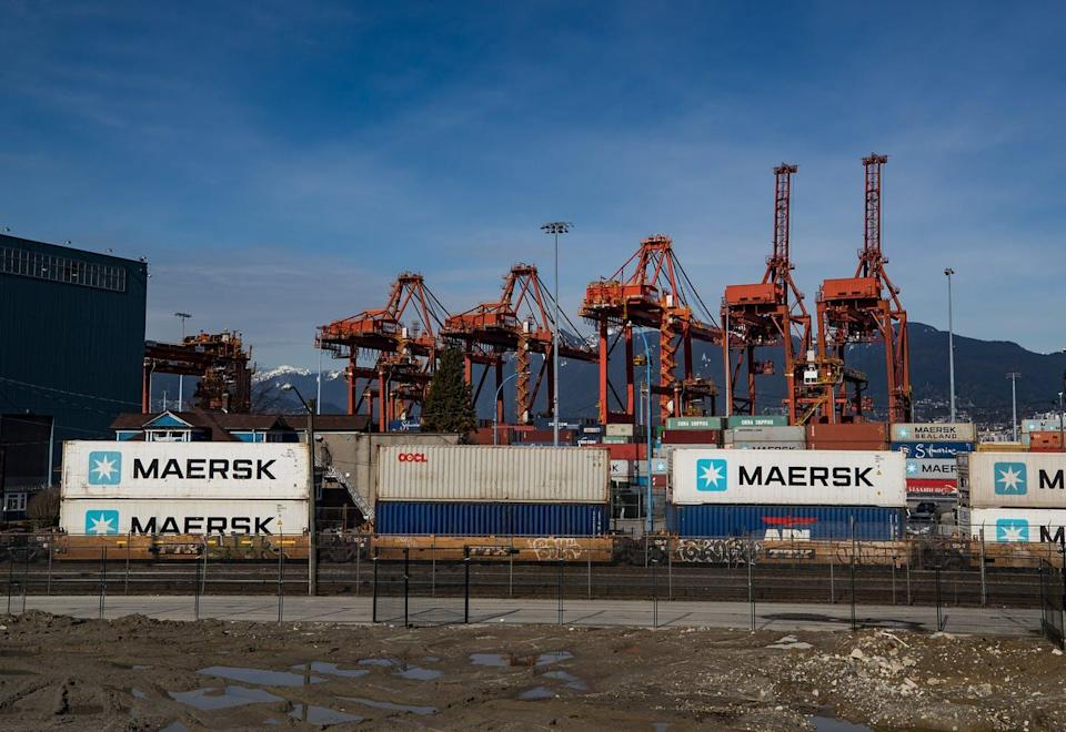 Stacked cargo containers in front of port cargo lifts.