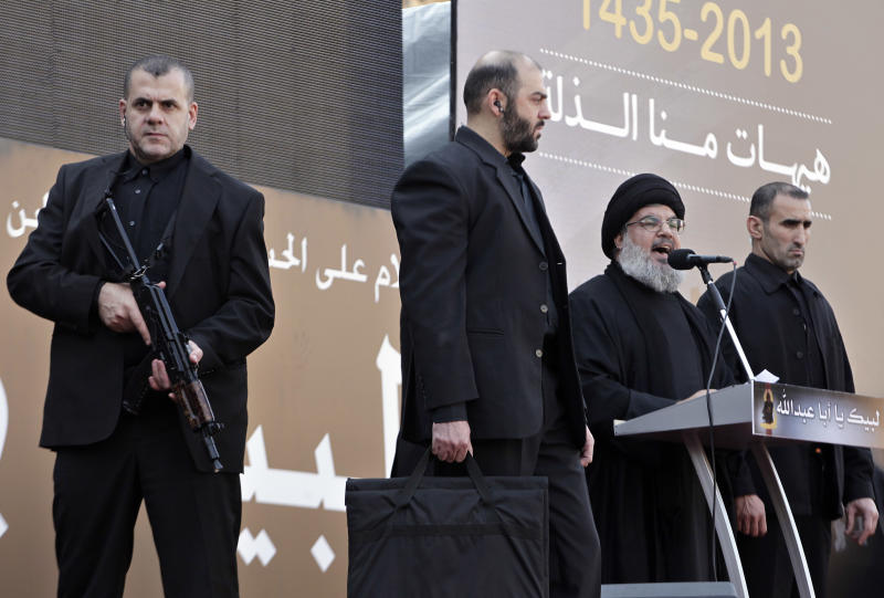 Hezbollah leader Sheik Hassan Nasrallah, second right, speaks to the crowd in a rare public appearance during Ashura, that marks the death of Shiite Islam's Imam Hussein, in the suburbs of Beirut, Lebanon, Thursday, Nov. 14, 2013. Nasrallah said, his fighters will continue to take part in the battles of Syria along with government forces as long as it is needed. (AP Photo/Bilal Hussein)