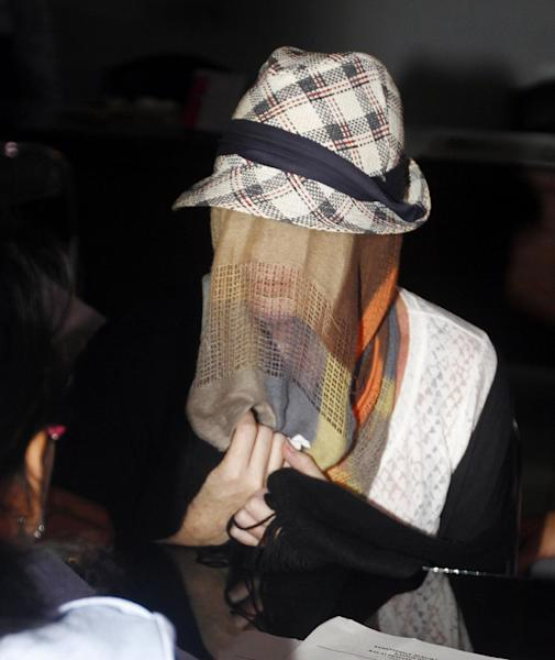 Australian Schapelle Corby, covering her face, listens to an official at the correctional office after she received her parole in Bali, Indonesia, Monday, Feb. 10, 2014. The Australian woman convicted of smuggling marijuana into Indonesia in 2005 has been released from jail on parole. She was convicted of smuggling 4.2 kilograms (9 pounds) of marijuana onto Bali and sentenced to 20 years in prison. (AP Photo/Firdia Lisnawati)
