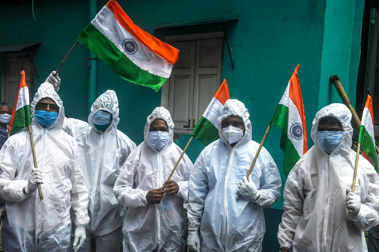 Frontline COVID-19 coronavirus warriors such as health workers, patients ambulance drivers, crematorium workers, wearing Personal Protective Equipment (PPE) suits hold Indian national flags as part of the Independence Day celebrations in Kolkata on August 15, 2020. - India's Prime Minister Narendra Modi issued a new warning to China over deadly border tensions on August 15, using his most important speech of the year to promise to build a stronger military. (Photo by Dibyangshu SARKAR / AFP) (Photo by DIBYANGSHU SARKAR/AFP via Getty Images)