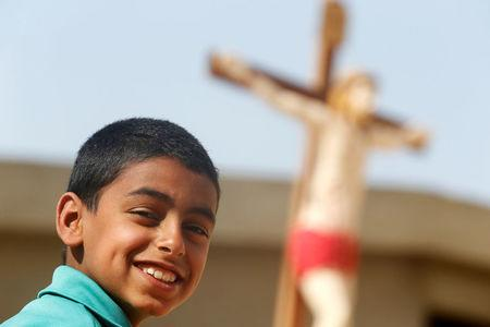A Christian boy who left from Al-Arish city North Sinai's Governorate capital after the escalation of a campaign targeting Christians by Islamic State militants last week, smiles near at scale model of Christ after arriving at the Saint Church in Ismailia, northeast of Cairo, Egypt February 27, 2017. Picture taken February 27, 2017. REUTERS/Amr Abdallah Dalsh
