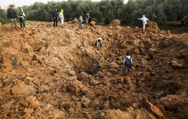 Palestinians examine the site of an Israeli air strike in Gaza on February 18, 2018