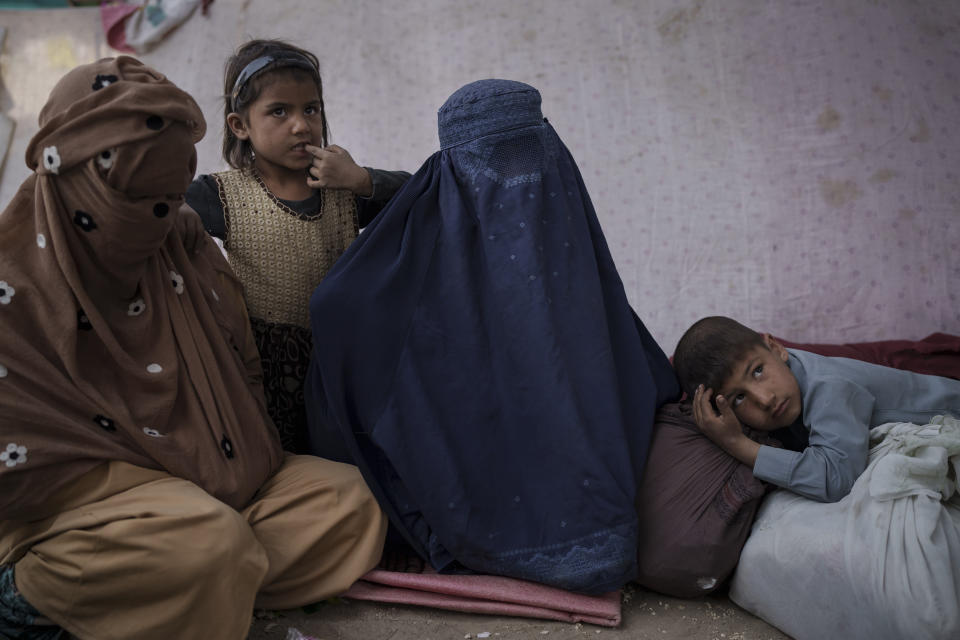 Malalai, center, from Kunduz province, sits with her children at a camp for internally displaced people as they wait for a bus to return home, in Kabul, Afghanistan, Saturday, Oct. 9, 2021. (AP Photo/Felipe Dana)