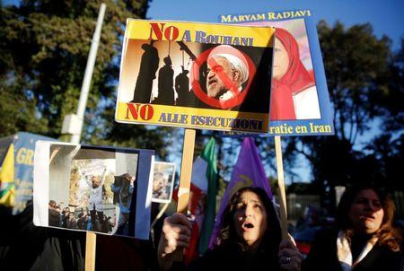 Opponents of Iranian President Hassan Rouhani hold a protest outside the Iranian embassy in Rome