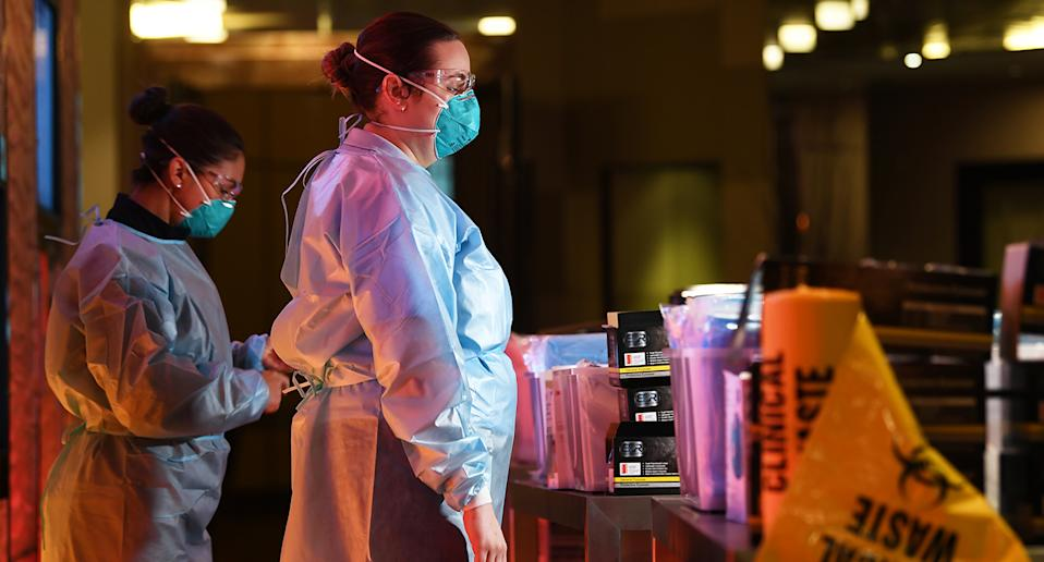 Health care workers are seen at a personal protective equipment station inside of the Grand Hyatt Melbourne on January 12. Source: AAP