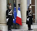 Black bows are attached to the French national flag and the European Union flag (left) at the Elysee Palace in Paris