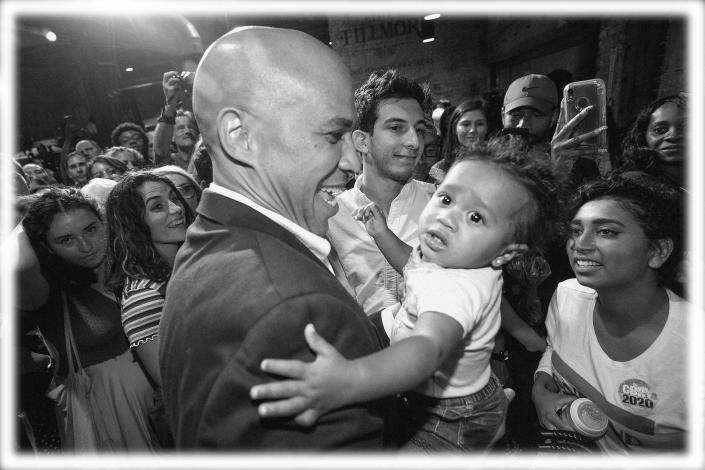 Sen. Cory Booker holds up a young child after an Aug. 7 rally in Philadelphia. (Photo: Charles Fox/The Philadelphia Inquirer via AP; digitally enhanced by Yahoo News)