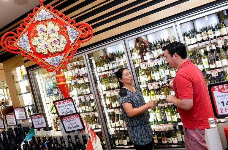 Store manager Will Figueira (R) talks to customer Sophie Liang in his liquor store in Sydney on January 30, 2013