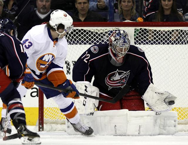 Columbus Blue Jackets' Sergi Bobrovsky, right, of Russia, stops a shot by New York Islanders' Mike Halmo in the second period of an NHL hockey game in Columbus, Ohio, Sunday, April 6, 2014. (AP Photo/Paul Vernon)