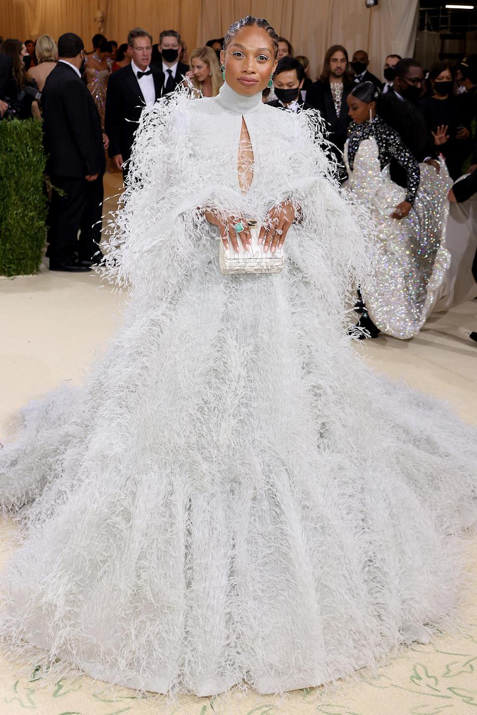 <p>After finishing her Olympic career in Tokyo, Felix tried on a dramatically different look, walking the Met carpet in a billowing feathered dress by Fendi.</p>