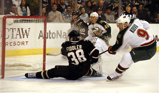 Dallas Stars forward Vernon Fiddler (38) slides into the net as Minnesota Wild forward Mikko Koivu (9) defends during the first period of an NHL hockey game Friday, March 29, 2013, in Dallas, Texas. (AP Photo/Sharon Ellman)