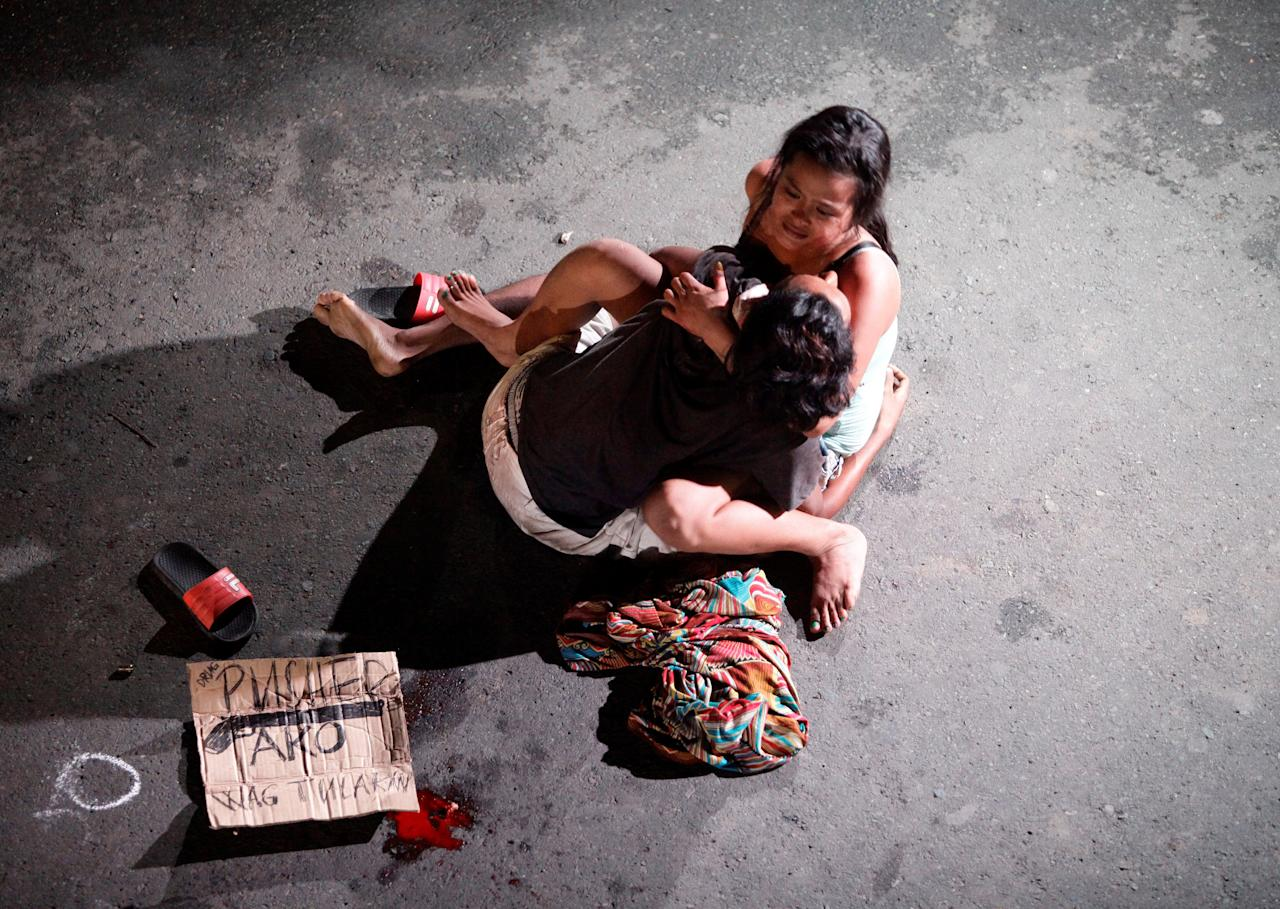 "ATTENTION EDITORS - VISUAL COVERAGE OF SCENES OF INJURY OR DEATHA woman cradles the body of her husband, who was killed on a street by a vigilante group, according to police, in a spate of drug related killings in Pasay city, Metro Manila, Philippines July 23, 2016. A sign on a cardboard found near the body reads: ""Pusher Ako"", which translates to ""I am a drug pusher.""     REUTERS/Czar Dancel     TPX IMAGES OF THE DAY"