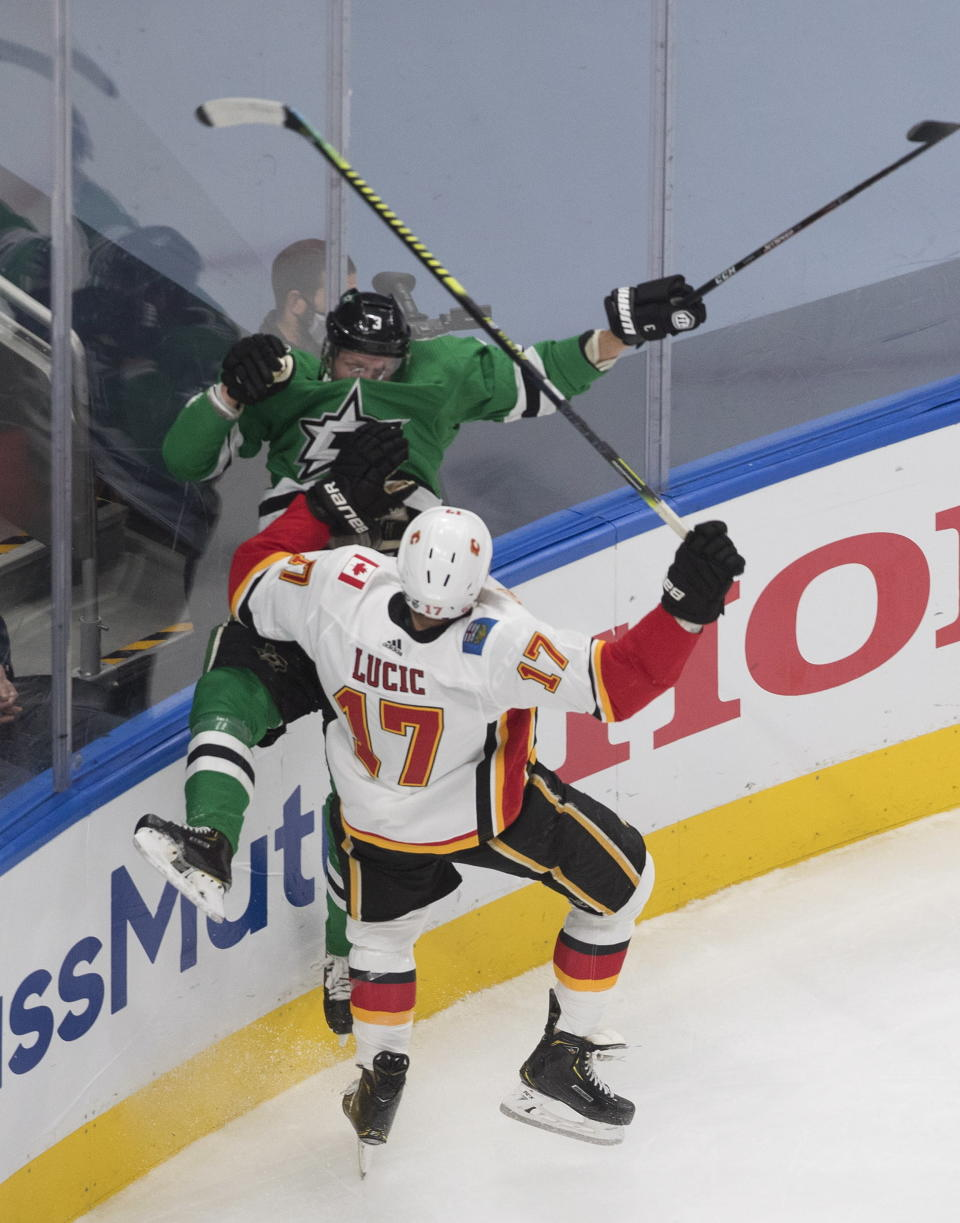 Calgary Flames' Milan Lucic (17) checks Dallas Stars' John Klingberg (3) during the first period of a first-round NHL Stanley Cup playoff hockey series in Edmonton, Thursday Aug. 13, 2020. (Jason Franson/The Canadian Press via AP)