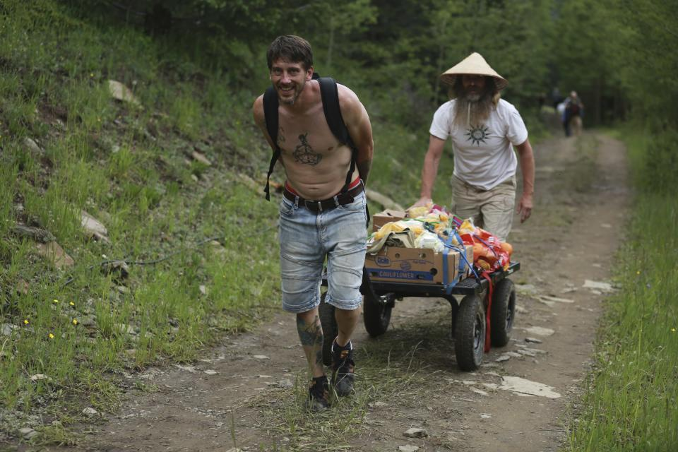 Rainbow Gathering participants carry food up a hill from the parking lot toward campsites on Friday, July 2, 2021, in the Carson National Forest, outside of Taos, N.M. More than 2,000 people have made the trek into the mountains of northern New Mexico as part of an annual counterculture gathering of the so-called Rainbow Family. While past congregations on national forest lands elsewhere have drawn as many as 20,000 people, this year's festival appears to be more reserved. Members (AP Photo/Cedar Attanasio)