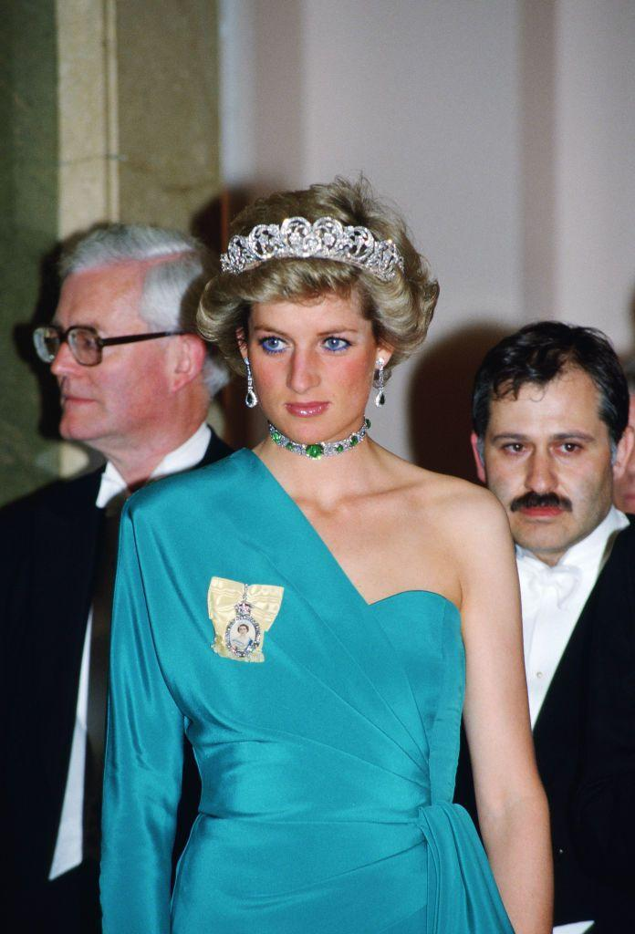 <p>While party-going at London's Claridges Hotel, the Princess of Wales pulled out all of the stops, jewelry-wise. She wore the Spencer tiara, Queen Mary's emerald and diamond choker necklace, and her Royal Order to complement her one-shouldered turquoise gown. </p>