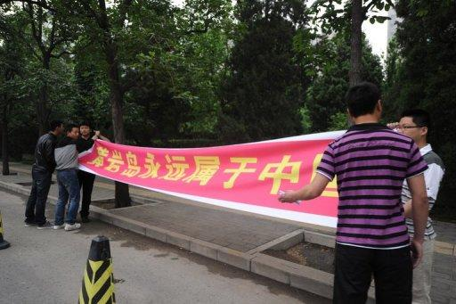 "Plainclothes policemen try to stop two protesters holding a banner that says, ""Huangyan island (Scarborough Shoal) will always belong to China"" outside the Philippines embassy in Beijing, on May 11. China told its citizens they were not safe in the Philippines and its state media warned of war, as a month-long row over rival claims in the South China Sea threatened to spill out of control"