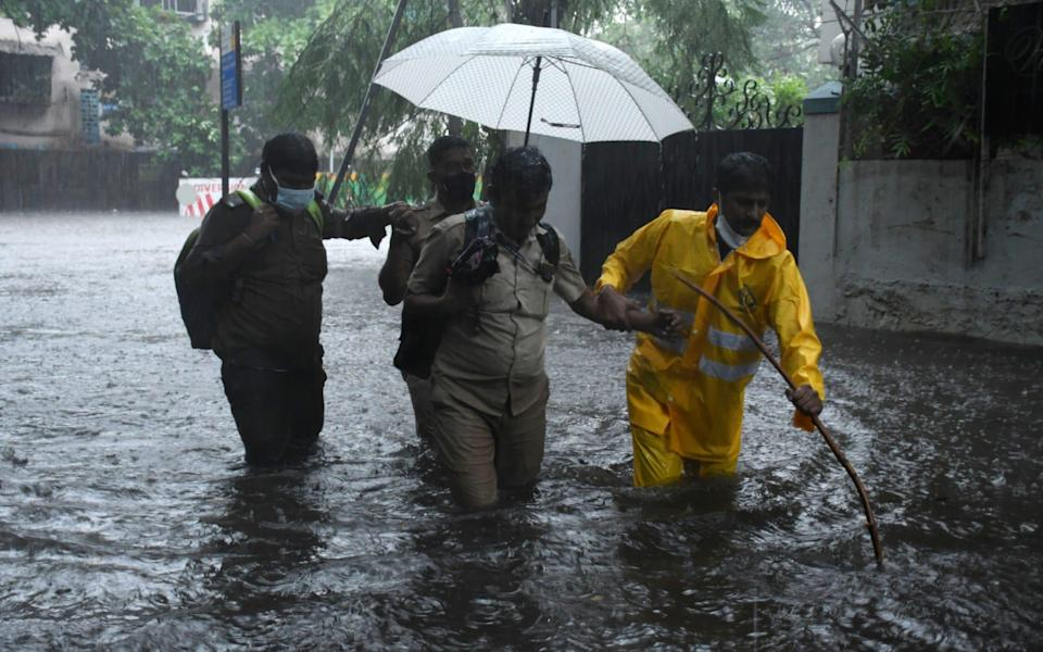 A policeman helps a driver cross a flooded street after his public transport bus became stuck due to heavy rain hit Mumbai - STR/EPA-EFE/Shutterstock