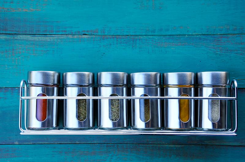 Steel spice rack hanging on a blue wooden wall.