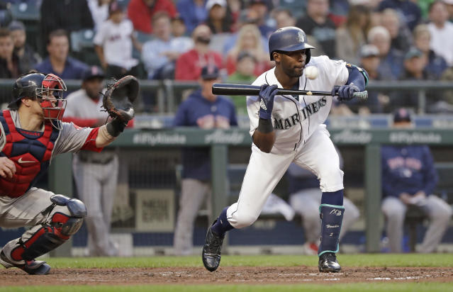 Seattle Mariners' Guillermo Heredia, right, pulls back from a bunt attempt and watches the ball go past toward Boston Red Sox cacher Christian Vazquez during the fifth inning of a baseball game Thursday, June 14, 2018, in Seattle. (AP Photo/Elaine Thompson)