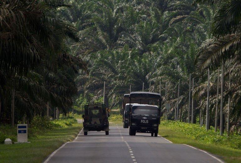 Malaysian police and an army truck are pictured in Lahad Datu on Borneo island, on March 3, 2013. Five Malaysian policemen and two gunmen have died in a fresh clash on Borneo island, as fears mounted that violence linked to a deadly standoff with Filipino intruders was spreading