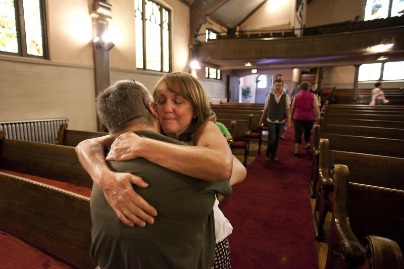 Gail Stevens, left, comforts Judy Goos, right, at the Grant Avenue United Methodist Church in Aurora, Colo. on Sunday, July 22, 2012. Goos arrived minutes after the movie theater shooting since her daughter Emma Goos, 19, was in theater nine and called her right after she called 911. When Goos and her husband arrived on scene they began to help a number of youths they knew through their children. (AP Photo/Barry Gutierrez)