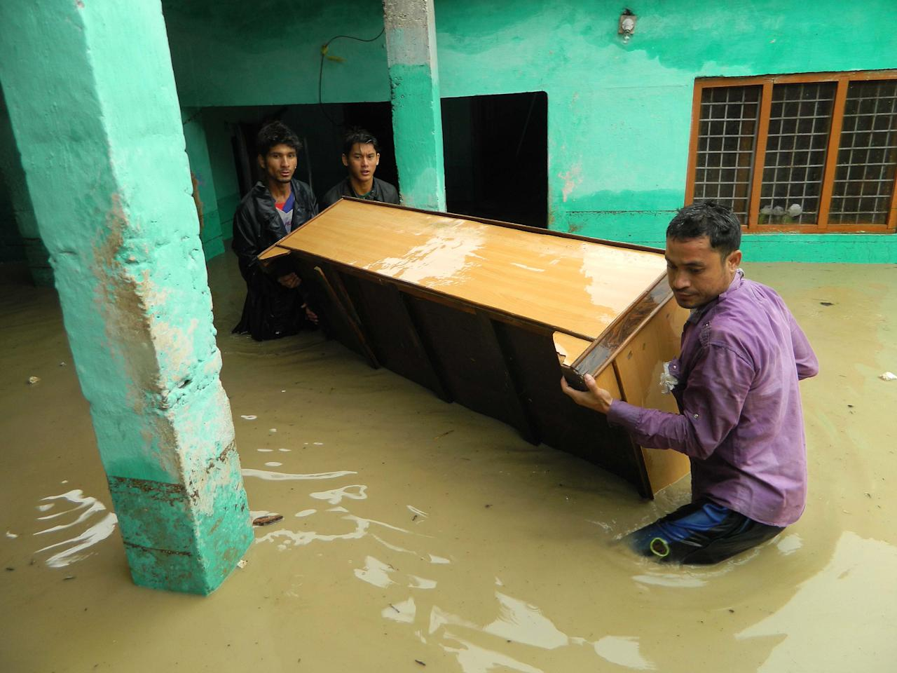 Indian people move furniture as homes floods due to the heavy rains in the northern state of Uttarakhand on June 17, 2013. Heavy rains lashed parts of north India June 17, resulting in the deaths of at least 26 people, as the annual monsoon covered the country nearly two weeks ahead of schedule, officials said.  AFP PHOTO        (Photo credit should read STR/AFP/Getty Images)