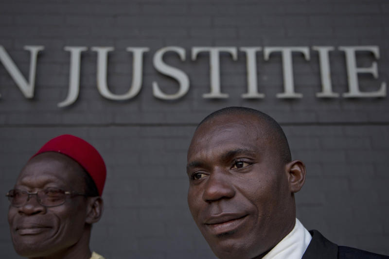 Alali Efanga, right, and Chief Fidelis A. Oguru, plaintiffs in the court case of Nigerian farmers against Shell, wait for the start of their case in The Hague, Netherlands, Thursday Oct. 11, 2012. Nigerian farmers are suing Shell in a Dutch court, asking judges to order the oil multinational to clean up environmental damage the farmers say is caused by leaking pipes. Thursday's case in The Hague Civil Court is a legal landmark in the Netherlands as it marks the first time a Dutch company has been sued for alleged environmental mismanagement caused by an overseas subsidiary. (AP Photo/Peter Dejong)