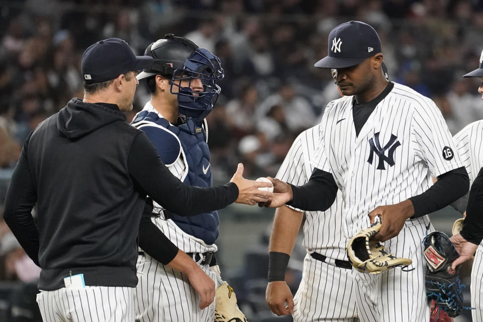 New York Yankees manager Aaron Boone, left, removes pitcher Domingo German in the ninth inning of a baseball game against the Tampa Bay Rays, Friday, Oct. 1, 2021, in New York. (AP Photo/Mary Altaffer)