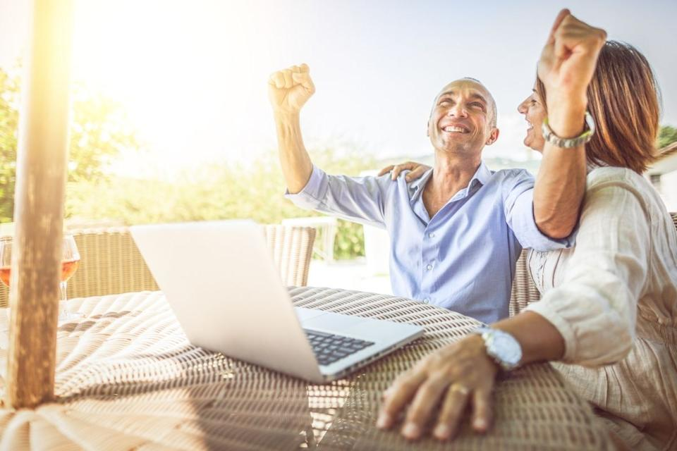 Mature couple celebrate lottery win on laptop. Source: Getty Images
