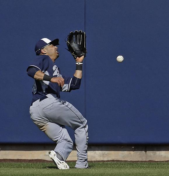 San Diego Padres' Rico Noel can't catch a triple hit by Milwaukee Brewers' Elian Herrera during the sixth inning of an exhibition baseball game Friday, March 7, 2014, in Phoenix. (AP Photo/Morry Gash)