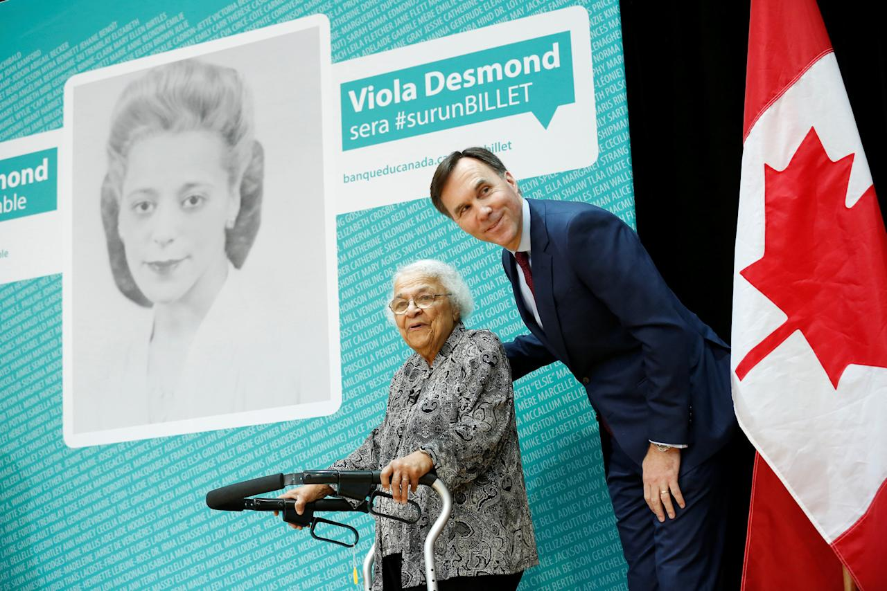 Canada's Finance Minister Bill Morneau stands with Wanda Robson after her sister Viola Desmond was chosen to be featured on a new $10 bank note during a ceremony at the Museum of History in Gatineau, Quebec, Canada, December 8, 2016. REUTERS/Chris Wattie     TPX IMAGES OF THE DAY