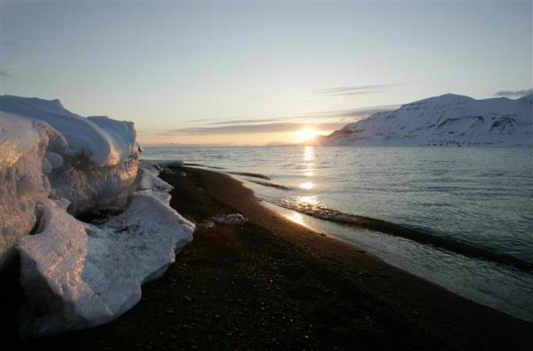 The sun shines low in the sky just after midnight over a frozen coastline near the Norwegian Arctic town of Longyearbyen, April 26, 2007.