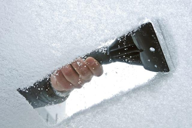 scraping snow and ice from the...