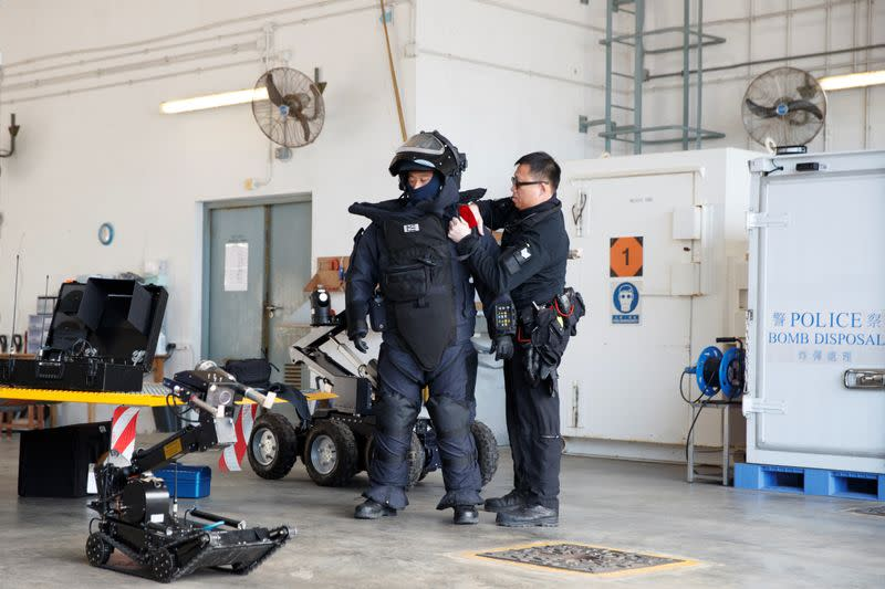 A colleague assists an EOD officer in putting on a protective suit during a media tour of the EOD depot of the Hong Kong police in Hong Kong