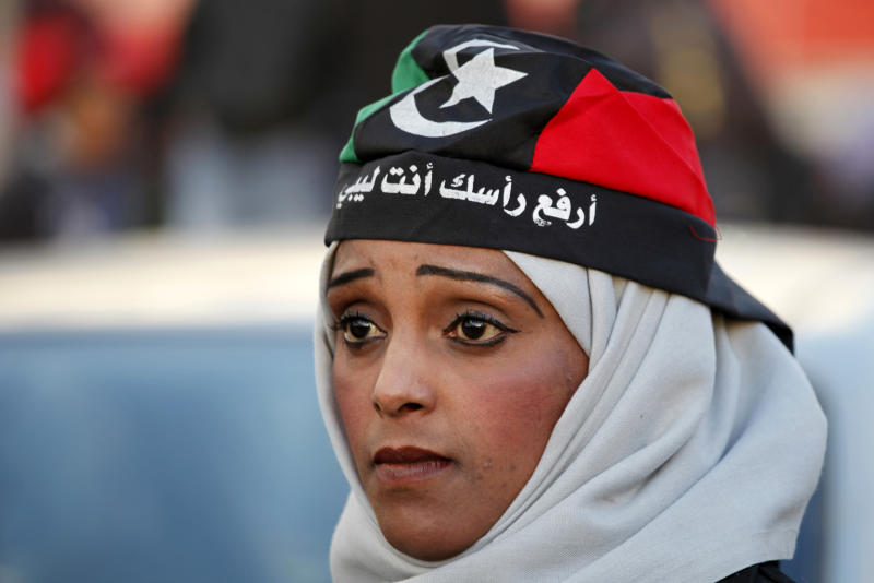 """FILE - In this Friday, Feb. 15, 2013 file photo, a Libyan woman wearing a depiction of the national flag bearing the words, """"hold your head high, you are Libyan,"""" attends commemorations to mark the second anniversary of the revolution that ousted Moammar Gadhafi in Benghazi, Libya. Women played a major role in the 8-month civil war against dictator Moammar Gadhafi, massing for protests against his regime, selling jewelry to fund rebels, helping treat the wounded, smuggling weapons across enemy lines to rebels. But since Gadhafi's fall more than 18 months ago, women have been rewarded by seeing rights they enjoyed under his rule hemmed in and restricted. (AP Photo/Mohammad Hannon, File)"""