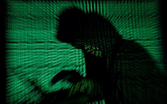 A hooded man holds a laptop computer as cyber code is projected on him - Kacper Pempel/Reuters