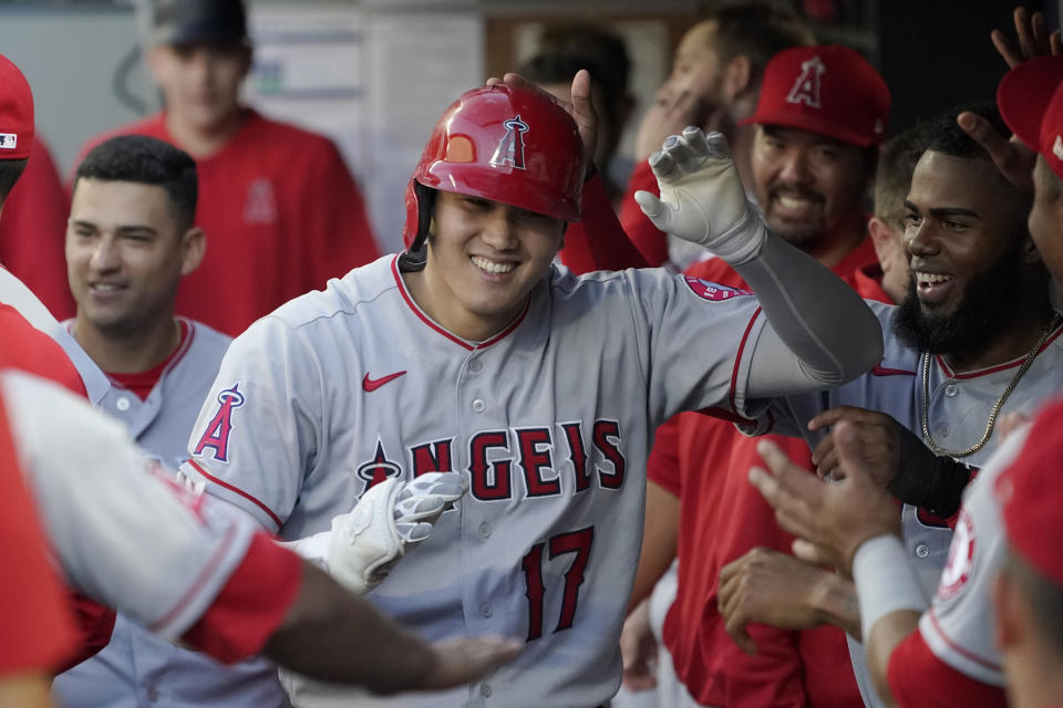 Los Angeles Angels' Shohei Ohtani is greeted in the dugout after he hit a solo home run during the third inning of the team's baseball game against the Seattle Mariners, Friday, July 9, 2021, in Seattle. (AP Photo/Ted S. Warren)