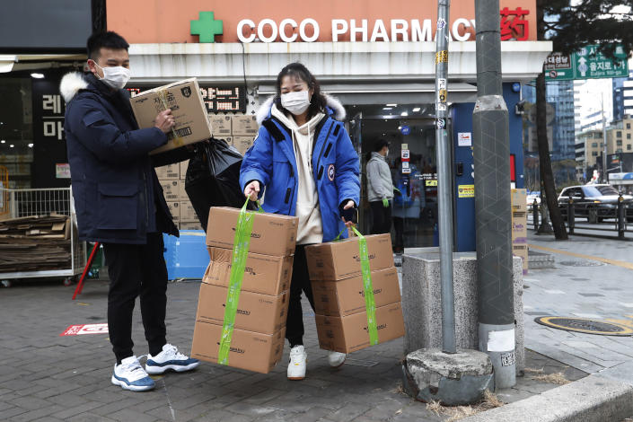 People leave after buying face masks at a pharmacy in Seoul, South Korea, Wednesday, Jan. 29, 2020. Countries began evacuating their citizens Wednesday from the Chinese city hardest-hit by an outbreak of a new virus that has killed 132 people and infected more than 6,000 on the mainland and abroad. (AP Photo/Ahn Young-joon)