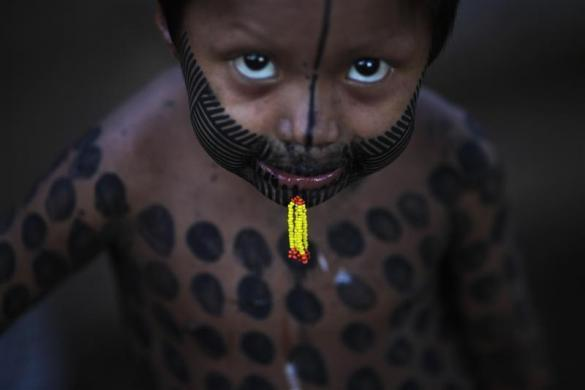 "A Kayapo boy with traditional body paint and piercing is seen at his home the day before the start of the ""Expedicionarios da Saude"" (Brazilian Health Expeditions), in the Kikretum community in Sao Felix, northern Brazil, April 21, 2011."