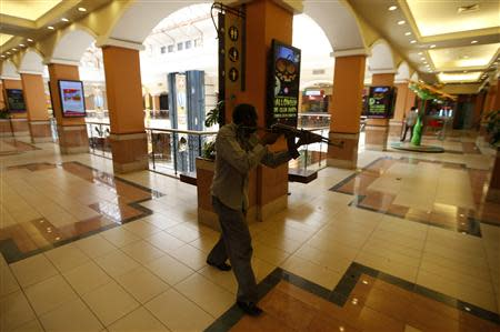 An armed police searches through a shopping centre for gunmen in Nairobi, September 21, 2013. REUTERS/Goran Tomasevic