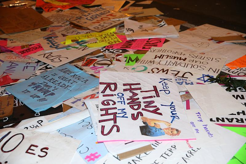Discarded signs from Women's March lie on streets around the corner from Trump Tower in New York City on Jan. 21, 2017. (Photo: Gordon Donovan/Yahoo News)