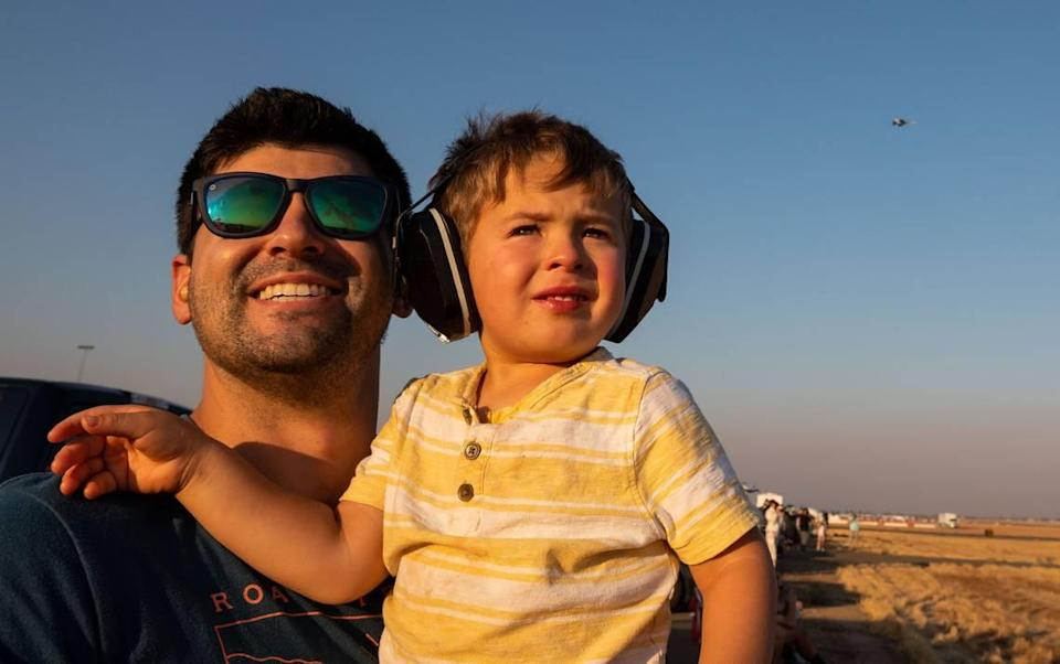 Roseville's William Weisman, left, holds his son, Jonathan Weisman, 2, to watch a an incoming plane prepare to cross another during the California Capital Airshow's Afterburnin' Drive-In Airshow on Friday, Sept. 24, 2021, at Mather Airport in Sacramento. The drive-in event, which offered more personal space and opportunity to bring food and drinks from home, was a first of its kind for the airshow.