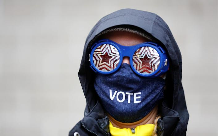 A woman wearing glasses and a face mask is seen outside a polling place in the CenturyLink Field Event Center, in Seattle - LINDSEY WASSON /REUTERS